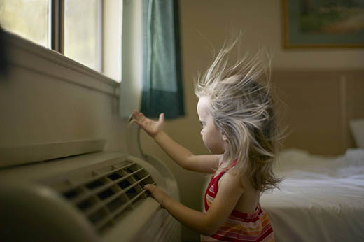 Girl standing in front of air conditioner