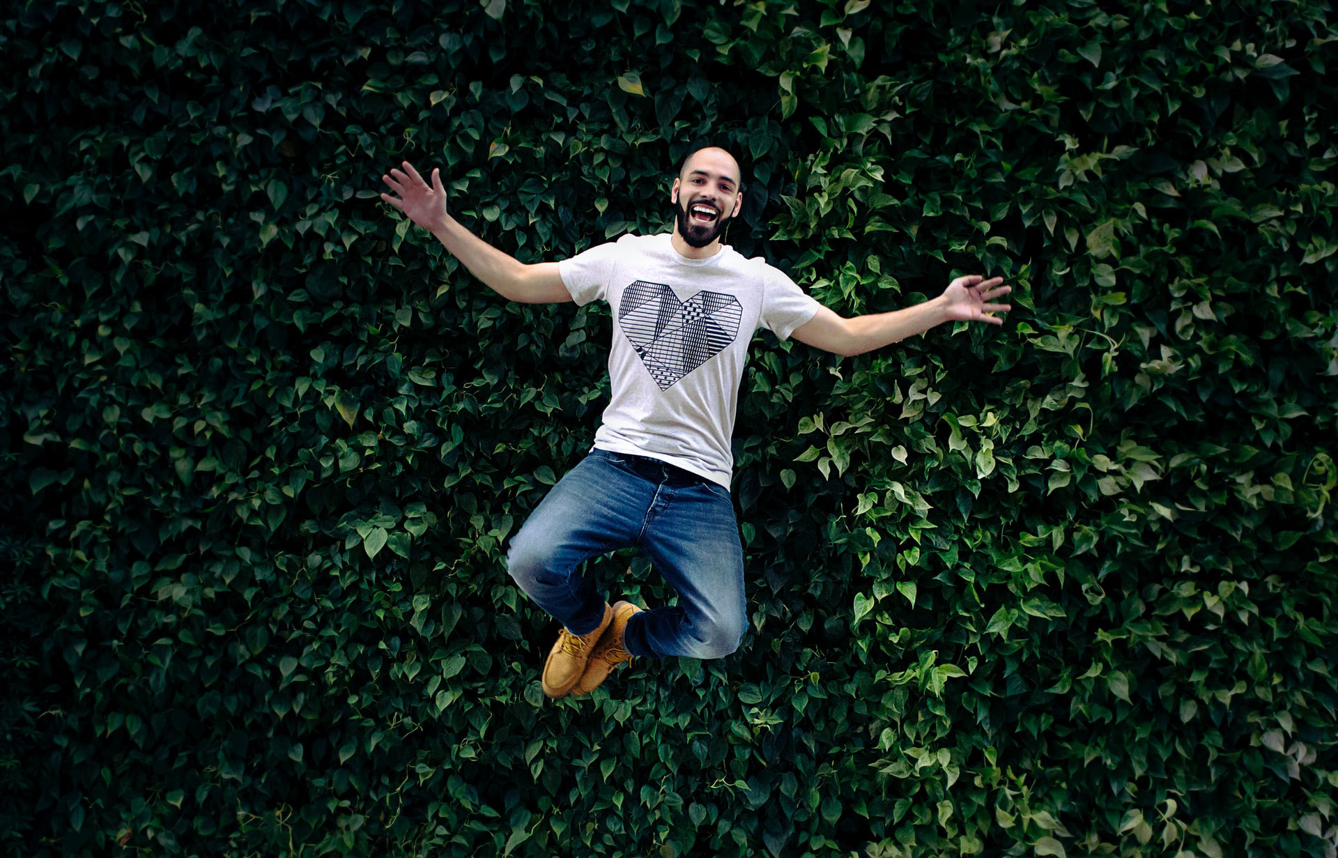 Man jumping with green hedge behind